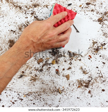 Hand with red sponge cleans a dirty surface - stock photo