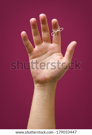 Hand With Remider String Tied On Index Finger Isolated Against Plum Background - stock photo
