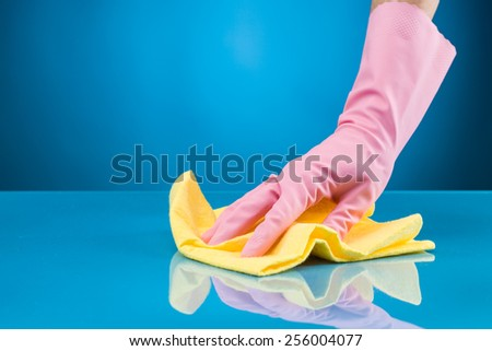 hand with rubber glove cleaning surface with microfiber cloth - stock photo