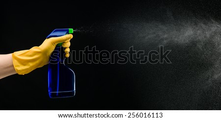 hand with rubber glove holding cleaning bottle and spraying liquid, on black background - stock photo