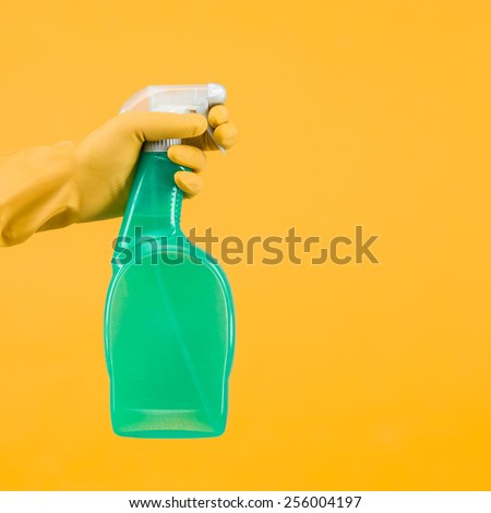 hand with rubber glove holding cleaning spray container on yellow background - stock photo