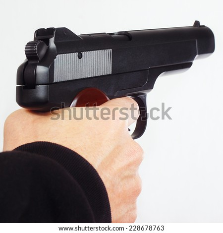 Hand with semi-automatic handgun on a white background - stock photo