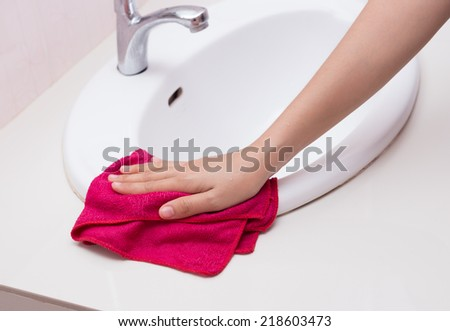 Hand with sponge cleaning white sink. - stock photo