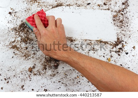 Hand with sponge cleans a dirty surface - stock photo