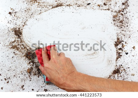 Hand with sponge cleans a heavily dirty surface - stock photo
