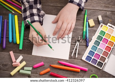 hand  with stationary on wooden background - stock photo