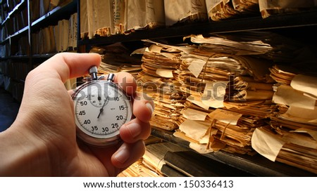 Hand with stopwatch, paper documents stacked in archive - stock photo