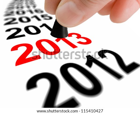 Hand with the game piece taking the next step to the new year 2013 - stock photo