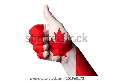 Hand with thumb up gesture in colored canada national flag as symbol of excellence, achievement, good, - for tourism and touristic advertising, positive political, social management of country - stock photo