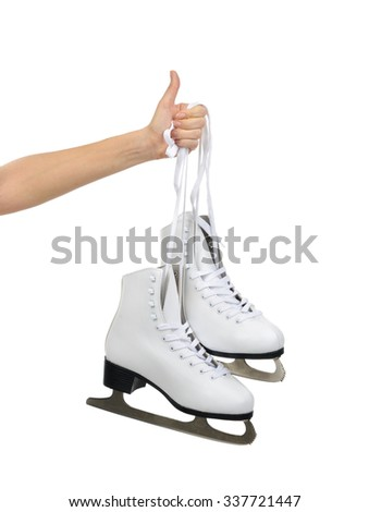 Hand with thumb up sign holding woman ice skates isolated on a white background - stock photo