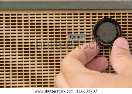 hand with tuner radio knob - stock photo