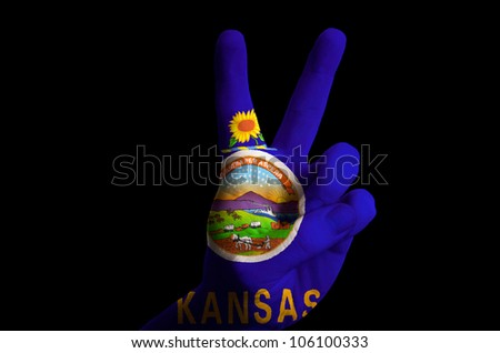 Hand with two finger up gesture in colored kansas state flag as symbol of winning, - for tourism and touristic advertising, positive political, cultural, social management of country - stock photo