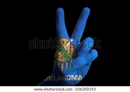 Hand with two finger up gesture in colored oregon oklahoma state flag as symbol of winning,  - for tourism and touristic advertising, positive political, cultural, social management of country - stock photo