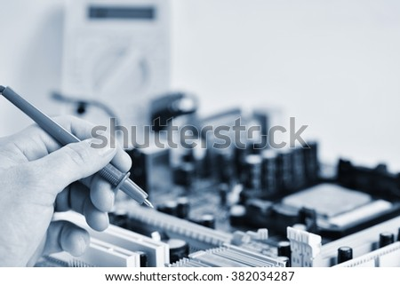 Hand with voltmeter above board with components.  Repair of computers and modern technologies. PCB. - stock photo