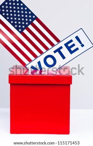 Hand with voting ballot and box on Flag of USA - stock photo