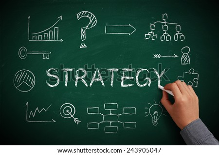 Hand with white chalk drawing strategy concept on chalkboard. - stock photo