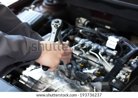 Hand with wrench. Auto mechanic in car repair - stock photo