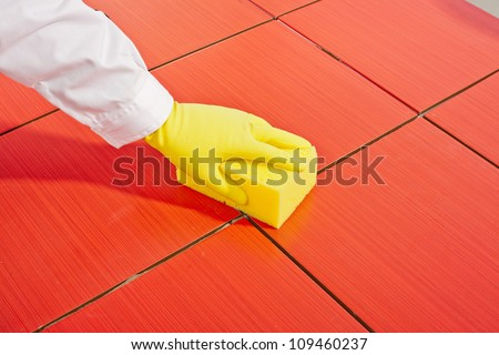 hand with yellow gloves and yellow  sponge clean red tiles - stock photo