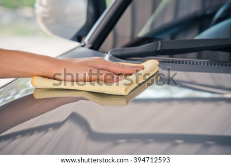 Hand with yellow microfiber cloth, cleaning car.  - stock photo