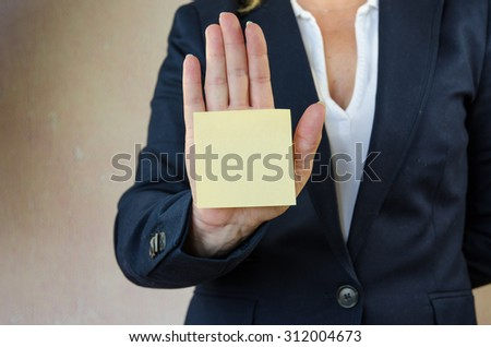 hand with yellow postit on it - stock photo