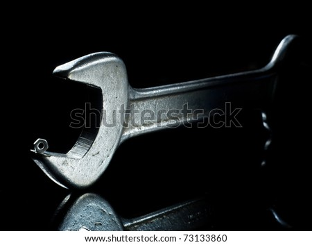 Hand wrench and small metal nut - stock photo