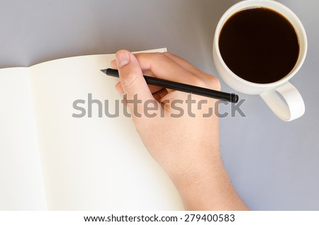 Hand write on the notebook with cup of coffee on table - stock photo
