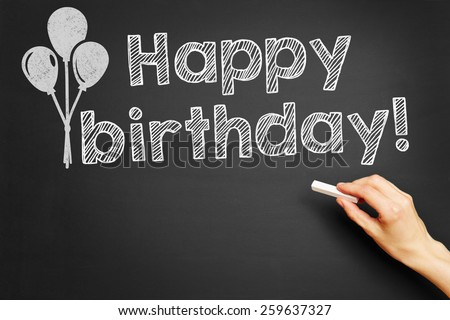 "Hand writes ""Happy birthday!"" on blackboard - stock photo"