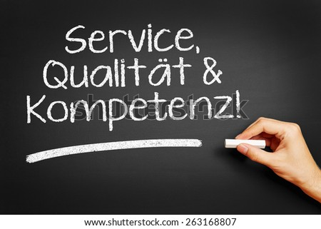 "Hand writes in German ""Service, Qualitaet & Kompetenz!"" (Service, quality & competence!) on blackboard - stock photo"