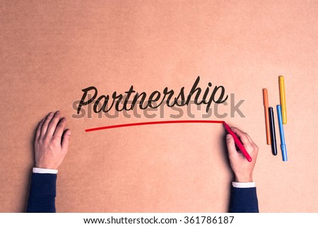 Hand writing a single word Partnership on paper - stock photo