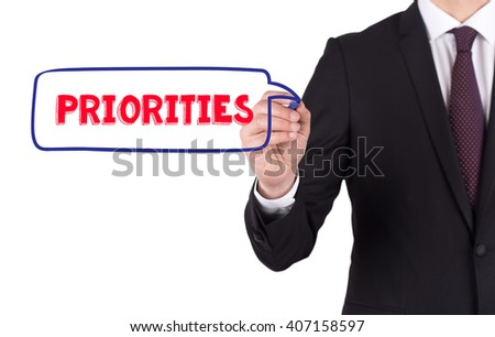 Hand writing a word PRIORITIES on white board - stock photo