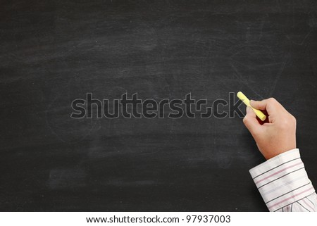 hand writing by yellow chalk on a blackboard. Useful as background space for text or image - stock photo