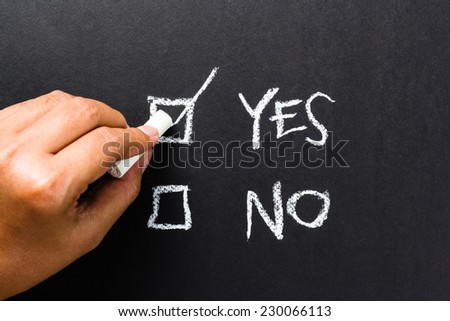Hand writing correct mark in the box of Yes or No choice - stock photo