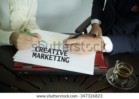 hand writing creative marketing text with two business person , business concept - stock photo