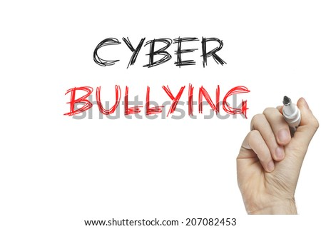 Hand writing cyber bullying on a white board - stock photo