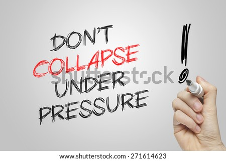 Hand writing don't collapse under pressure on grey background - stock photo