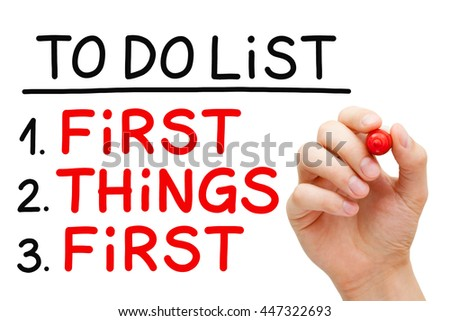 Hand writing First Things First in To Do List with red marker isolated on white. - stock photo
