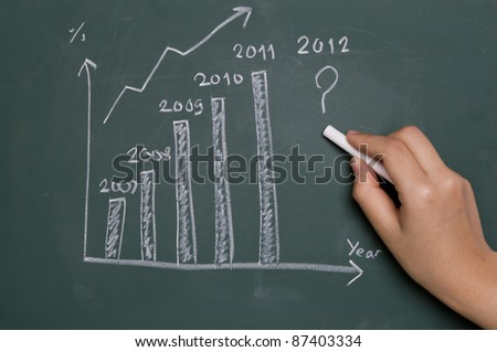 Hand writing graph on chalkboard - stock photo
