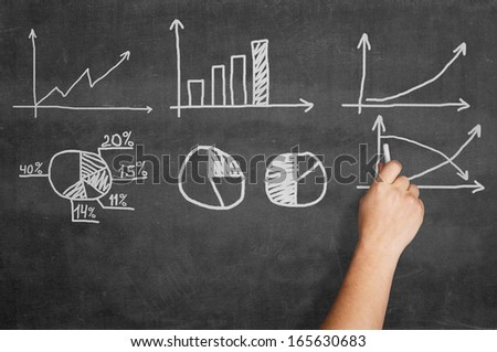 Hand writing graphs on blackboard  - stock photo