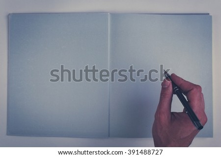 hand writing in empty book - holding pencil over blank page of a empty book  - (vintage color tone) - stock photo