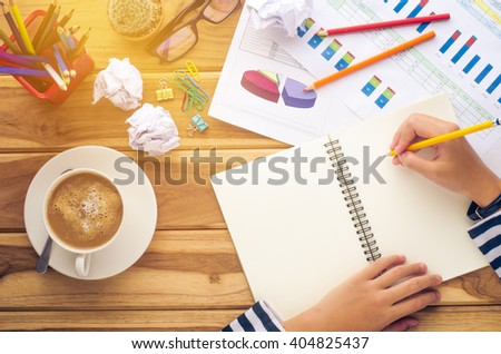 Hand writing in open notebook on table at morning  - stock photo