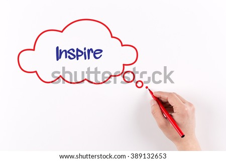 Hand writing Inspire on white paper, view from above - stock photo