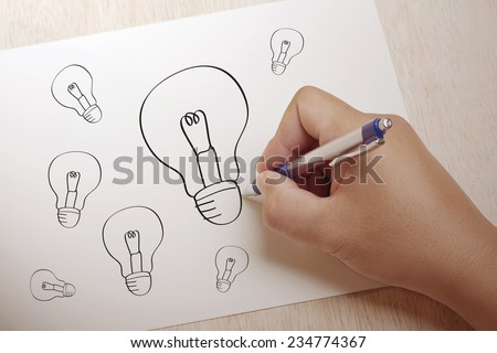 Hand writing Light bulb  on paper - stock photo