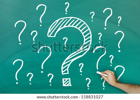Hand writing lots of questions on green blackboard - stock photo