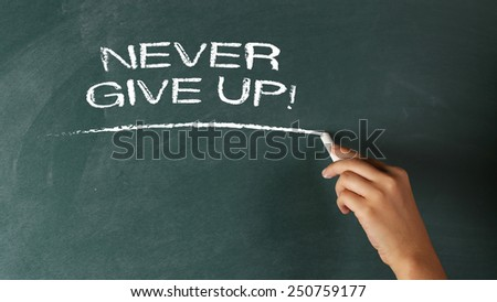 Hand writing Never Give Up! - Motivation Concept on a blackboard - stock photo