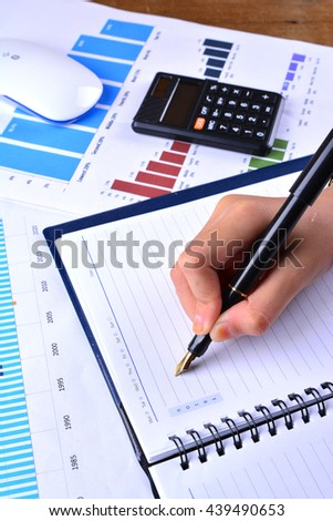 Hand writing on blank notebook with graph, chart, keyboard, mouse and calculator on wooden table - stock photo
