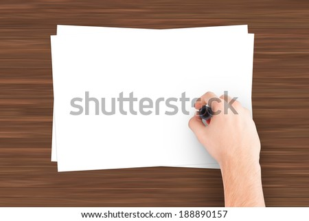 Hand writing on blank white note paper on wooden table. - stock photo