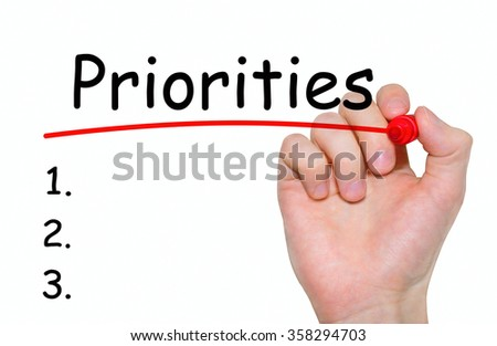 Hand writing Priorities with red marker on transparent wipe board, business concept - stock photo