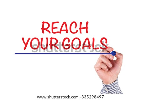 Hand writing REACH YOUR GOALS on whiteboard - stock photo