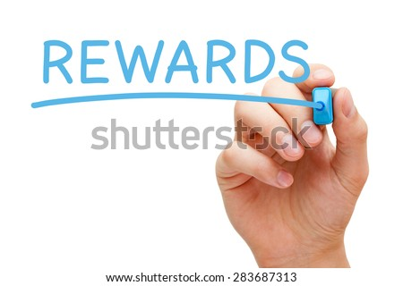 Hand writing Rewards with blue marker on transparent wipe board. - stock photo