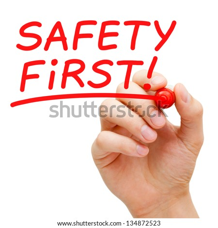 Hand writing Safety First with red marker on transparent wipe board. - stock photo